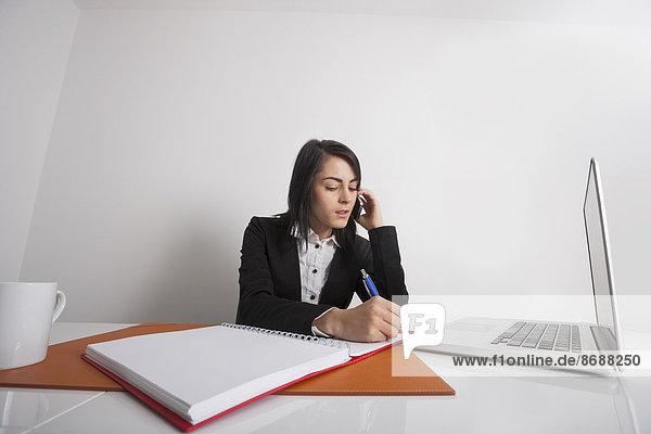 benutzen  Geschäftsfrau  Schreibtisch  schreiben  Telefon  Büro  Handy