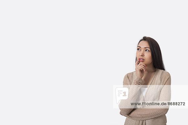 stehend junge Frau junge Frauen grau Hintergrund Nachdenklichkeit
