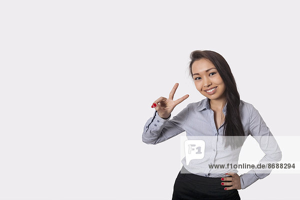 zeigen Portrait Geschäftsfrau Fröhlichkeit grau Zeichen Hintergrund Sieg Gewinn Signal