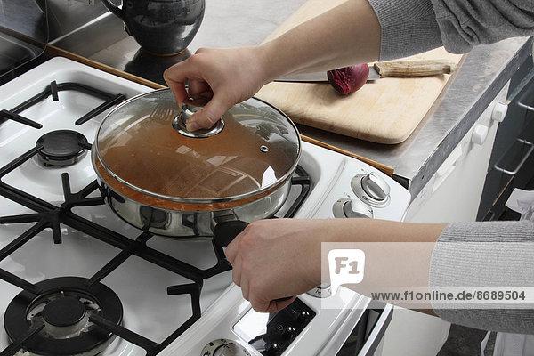 Putting a lid on a saucepan of simmering chicken rogan josh