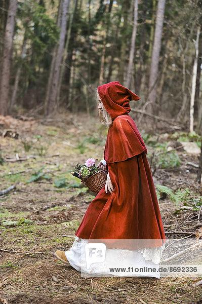 Mädchenmaskerade als Rotkäppchen im Wald unterwegs