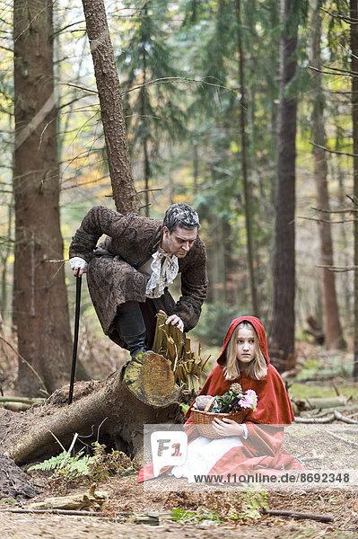 Mann  der das Wolfsbegegnungsmädchen verkleidet als Rotkäppchen repräsentiert.