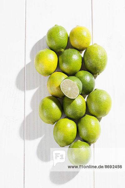 Limetten und Blätter auf Holztisch