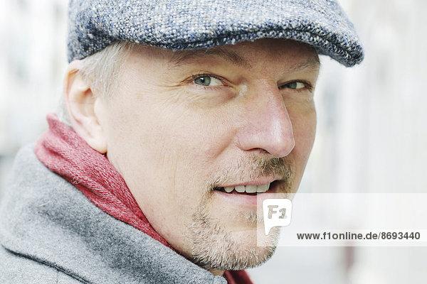 Porträt eines lächelnden Mannes mit Mütze