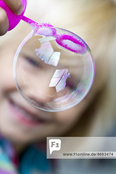 Smiling little girl with soap bubble