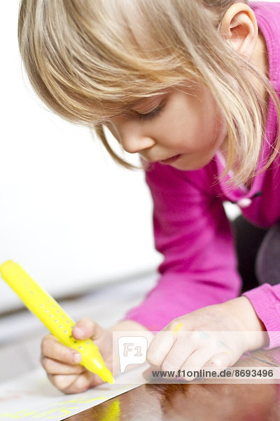 Portrait of little girl painting with yellow felt tip pen