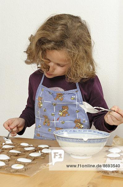 Kleines Mädchen breitet Zimtsterne mit Zuckerguss aus