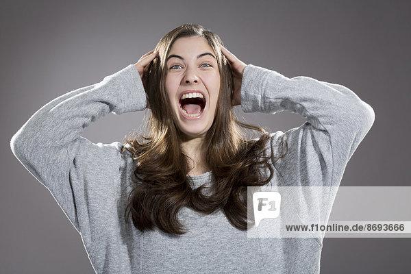 Porträt einer schreienden jungen Frau  Studioaufnahme