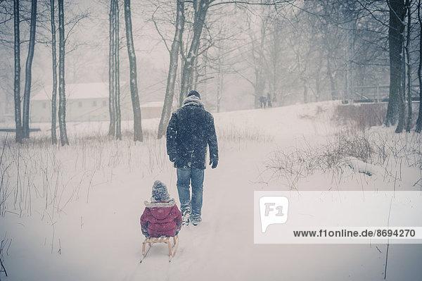 Vater zieht Schlitten mit Sohn im Schnee
