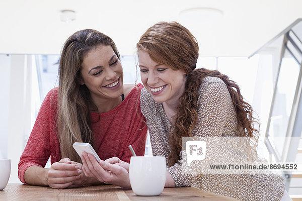 Zwei Frauen zu Hause mit Smartphone