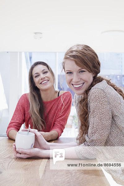 Zwei Frauen sitzen zu Hause am Tisch