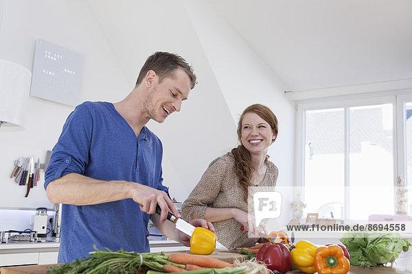 Junges Paar bei der Zubereitung von Speisen in der Küche