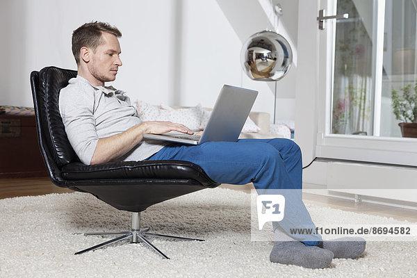 Mann zu Hause entspannt im Sessel mit Laptop