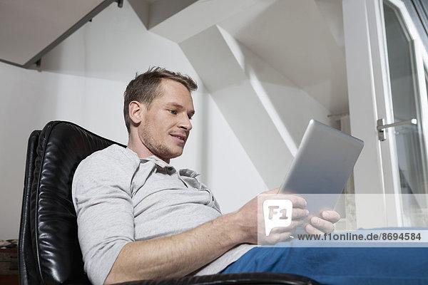 Mann zu Hause entspannt im Sessel mit Tablet-Computer