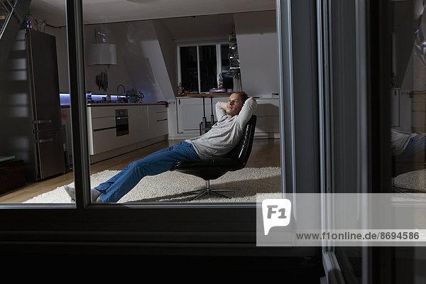 Mann zu Hause entspannt im Sessel bei Nacht