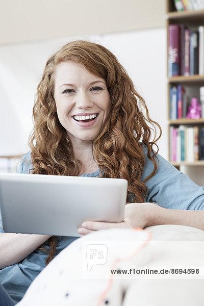 Porträt einer jungen Frau  die sich mit einem Tablet-Computer auf einer Couch in ihrer Wohnung entspannt.