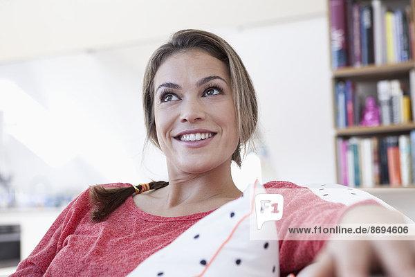 Porträt einer lächelnden Frau  die sich auf einer Couch in ihrer Wohnung entspannt.
