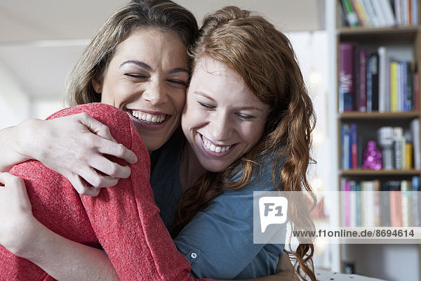 Zwei junge Freundinnen zu Hause  die sich umarmen.