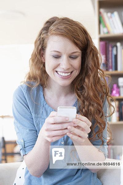 Junge Frau mit Smartphone zu Hause
