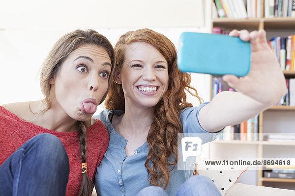 Zwei junge Freundinnen beim Fotografieren mit dem Smartphone