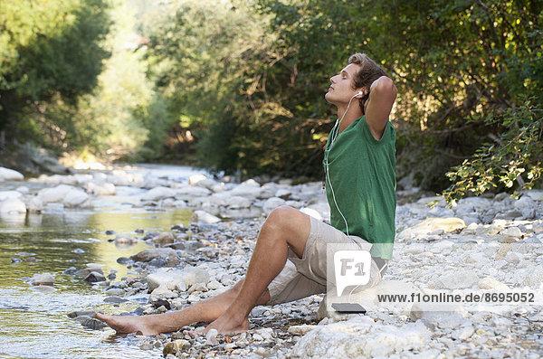 Österreich  Salzkammergut  Mondsee  junger Mann mit Kopfhörer zum Entspannen am Bach