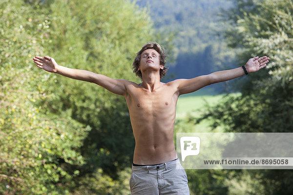 Österreich  Salzkammergut  Mondsee  Porträt eines jungen Mannes mit ausgestreckten Armen
