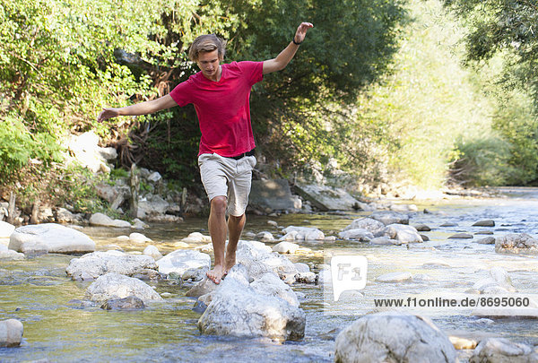 Austria  Salzkammergut  Mondsee  young man crossing a brook