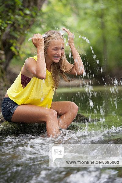 Austria  Salzkammergut  Mondsee  teenage girl refreshing at a brook