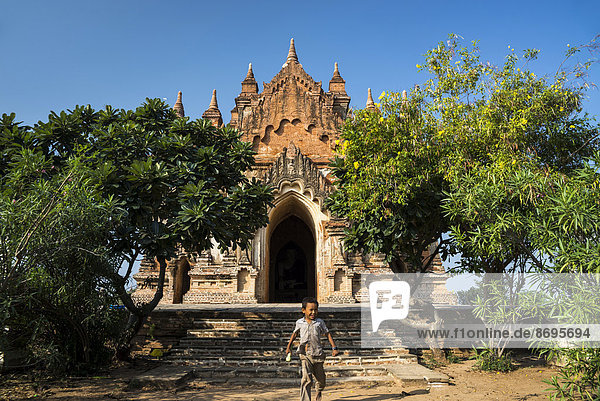 Boy in front of a temple  stupa or pagoda in the temple complex of the Plateau of Bagan  Mandalay Division  Myanmar or Burma
