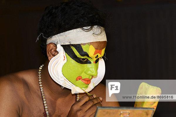 Kathakali-Tänzer beim Schminken  in der Vorbereitung auf seinen Auftritt  Kochi  Kerala  Südindien  Indien