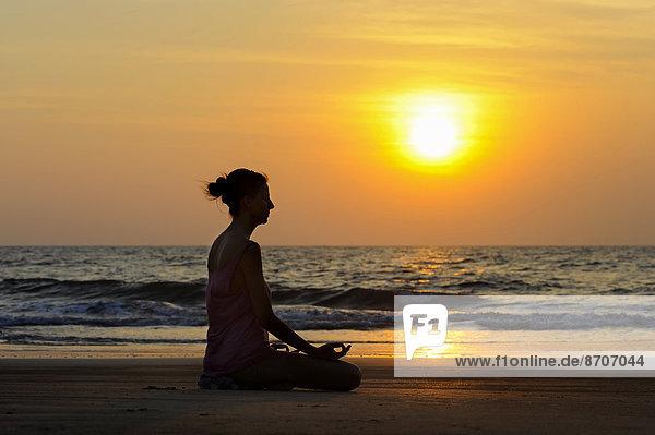 Frau meditiert bei Sonnenuntergang am Strand  Kerala  Indien