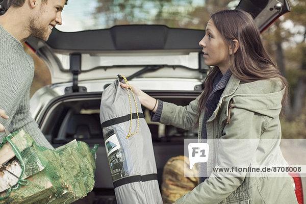 Seitenansicht des Paares  das die Campingausrüstung gegen das Auto hält.