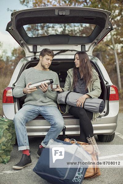 Mann gießt Kaffee für Frau beim Sitzen am Kofferraum während des Zeltens