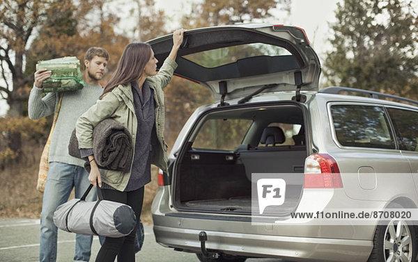 Frau schließt den Kofferraum beim Zelten mit Mann