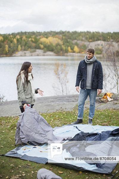 Paar kommuniziert beim Aufbau des Zeltes am Seeufer