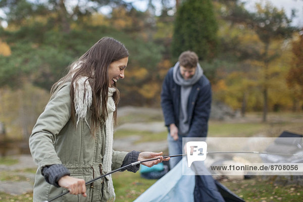 Junge Frau hält Zeltstange mit Mann im Wald