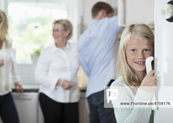 Porträt des lächelnden Mädchens mit Türgriff und Familie im Hintergrund in der Küche