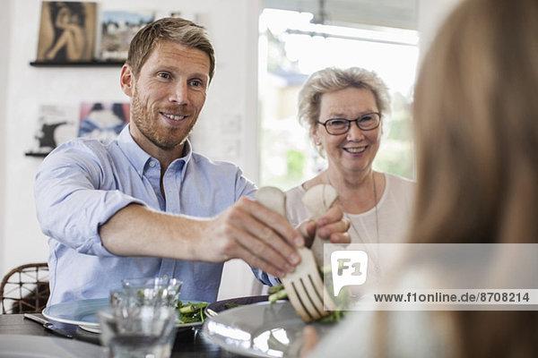 Lächelnder Mann serviert dem Mädchen zu Hause Salat.