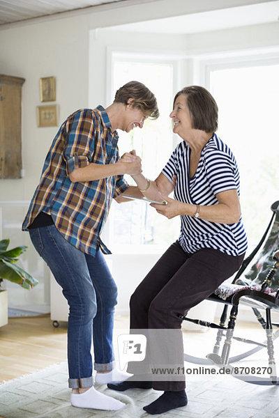 Reife Frau hilft Mutter beim Aufstehen vom Stuhl zu Hause