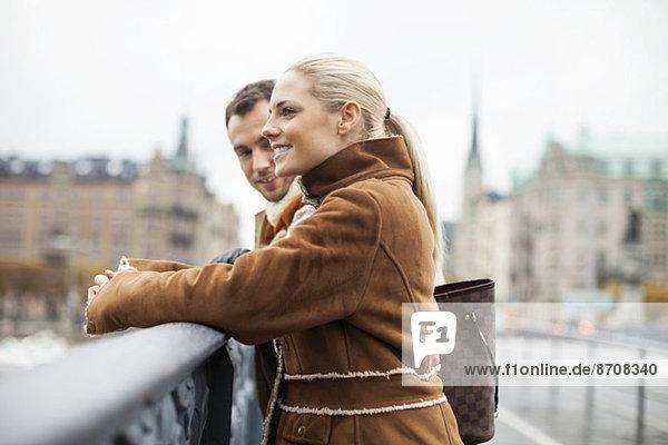 Seitenansicht des auf der Brücke stehenden Paares