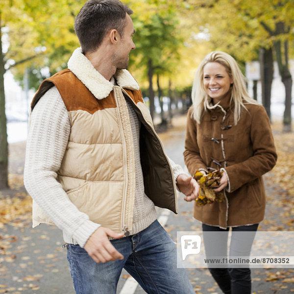 Verspieltes junges Paar auf der Straße im Herbst
