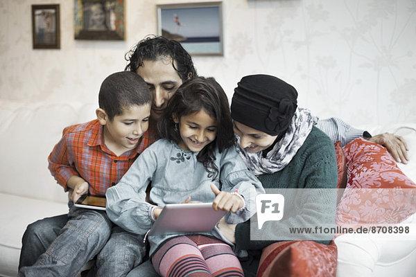 Muslimische Familie mit digitalem Tablett zusammen im Wohnzimmer