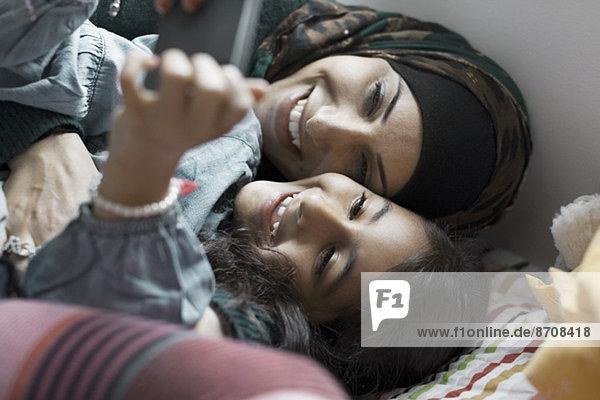 Verspielte Mutter und Tochter mit dem Handy im Schlafzimmer