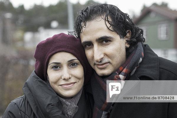Porträt eines lächelnden Paares im Freien im Winter