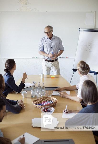 Senior Geschäftsmann im Gespräch mit Kollegen im Vorstandszimmer