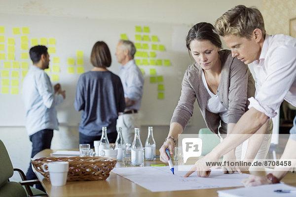 Geschäftsleute diskutieren über Blaupause am Konferenztisch