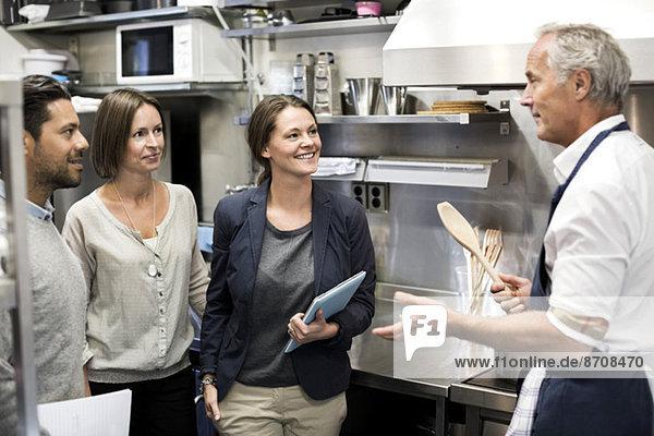Team von Inspektoren im Gespräch mit dem Chefkoch in der Großküche