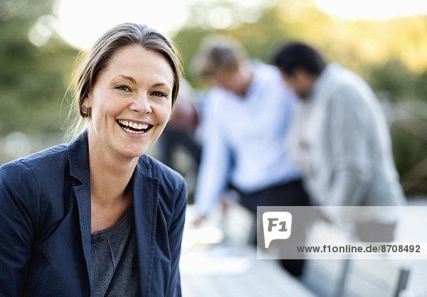 Porträt einer Geschäftsfrau  die mit Kollegen im Hintergrund auf der Terrasse lacht.