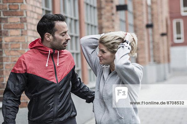 Sportliches Paar kommuniziert auf der Straße