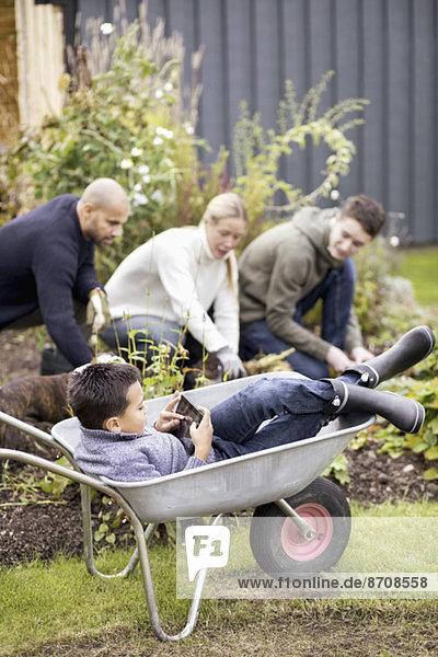Junge mit digitalem Tablett im Schubkarren sitzend mit Familien-Gartenarbeit im Hintergrund